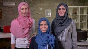 Ragazze musulmane AR di Enjouable che esaminano macchina fotografica nel hijab dei colori grigi e blu di rosa, fondo moderno del  stock footage