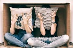 Ragazze nascoste dietro un cuscino Fotografia Stock Libera da Diritti