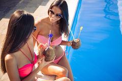 Ragazze nei cocktail e nel gossip beventi del bikini all'aperto Fotografie Stock
