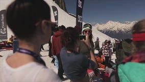 Ragazze in occhiali da sole, camicia alla stazione sciistica in montagne nevose Giorno pieno di sole pubblici video d archivio