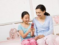 Ragazze in pigiami nell'invio di messaggi di testo della camera da letto fotografia stock libera da diritti