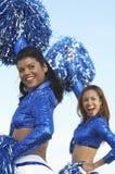 Ragazze pon pon che incoraggiano in uniforme blu immagine stock