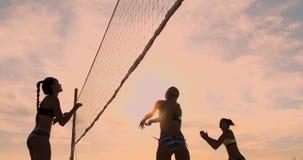 Ragazze sexy di pallavolo nel gioco del bikini sulla spiaggia nella pallavolo di estate sulla sabbia al tramonto al rallentatore stock footage