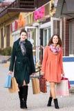 Ragazze sorridenti che camminano sulla via con i pacchetti Fotografie Stock Libere da Diritti