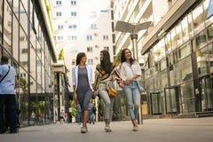 Ragazze sorridenti che camminano sulla via con i sacchetti della spesa Fotografia Stock