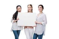 Ragazze sorridenti che giudicano insegna in bianco isolata su bianco Immagini Stock Libere da Diritti