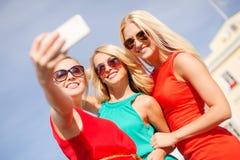 Ragazze sorridenti che prendono foto con la macchina fotografica dello smartphone Fotografia Stock Libera da Diritti