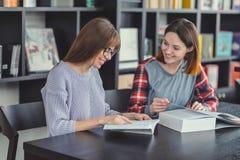 Ragazze sorridenti con il computer portatile in una libreria Immagine Stock
