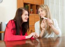Ragazze sorridenti con il test di gravidanza Immagini Stock