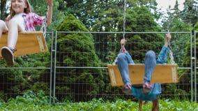Ragazze sorridenti divertendosi al campo da giuoco Bambini che giocano all'aperto di estate Adolescenti che guidano su un'oscilla video d archivio