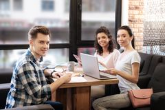 Ragazze sorridenti e funzionamento dell'uomo mentre sedendosi alla tavola Fotografia Stock Libera da Diritti