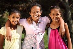Ragazze sorridenti felici del banco dell'abbraccio tre di amicizia Fotografia Stock