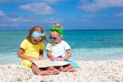 Ragazze sveglie adorabili con la grande mappa sulla spiaggia tropicale Fotografia Stock Libera da Diritti