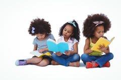 Ragazze sveglie che si siedono sui libri di lettura del pavimento Fotografia Stock Libera da Diritti