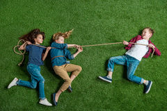 Ragazze sveglie e ragazzo che si trovano sull'erba e che giocano conflitto Fotografie Stock