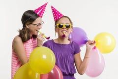Ragazze teenager ad un partito Ragazze su un fondo bianco, in cappelli festivi, soffianti nei tubi Fotografie Stock