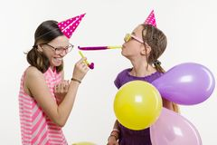 Ragazze teenager ad un partito Ragazze su un fondo bianco, in cappelli festivi, soffianti nei tubi, coriandoli variopinti Fotografia Stock Libera da Diritti