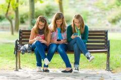 Ragazze teenager che per mezzo dei loro telefoni cellulari Fotografia Stock