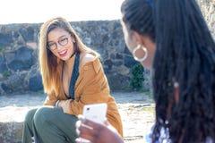 Ragazze teenager con il dispositivo mobile digitale all'aperto Fotografia Stock
