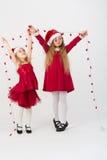 Ragazze in un vestito rosso in cappucci Santa Claus che tiene una ghirlanda Immagini Stock Libere da Diritti