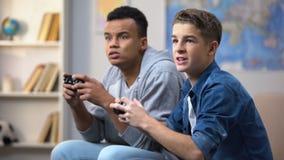 Ragazzi afroamericani ed europei felici di vincere attività di tempo libero del video gioco video d archivio