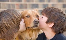Ragazzi che baciano un cane Immagini Stock