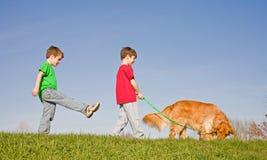 Ragazzi che camminano il cane Immagini Stock Libere da Diritti