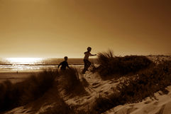 Ragazzi che funzionano in dune immagine stock libera da diritti