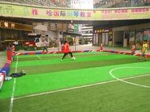 Ragazzi che giocano a calcio dentro un centro commerciale in un campo di calcio dell'interno Fotografie Stock