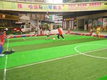 Ragazzi che giocano a calcio dentro un centro commerciale in un campo di calcio dell'interno Immagini Stock Libere da Diritti