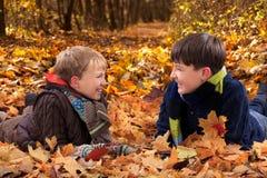 Ragazzi che giocano in fogli di autunno Fotografia Stock