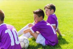 Ragazzi che guardano il gioco di calcio sul campo sportivo Immagine Stock
