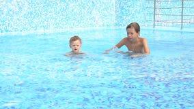 Ragazzi che nuotano nello stagno alla località di soggiorno archivi video
