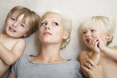 Ragazzi che si trovano con la madre su tappeto Fotografie Stock