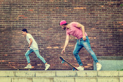 Ragazzi del skateboarder dal muro di mattoni Fotografia Stock