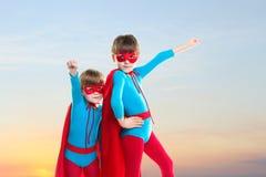 Ragazzi del supereroe al fondo del cielo di tramonto fotografia stock libera da diritti