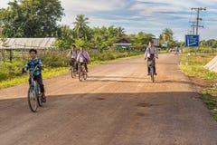 Ragazzi di scuola sulle biciclette in Muang Khong, Laos Fotografia Stock