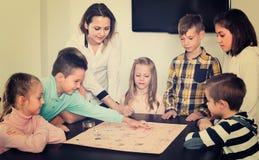Ragazzi e bambine che giocano al gioco da tavolo fotografia stock libera da diritti