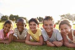 Ragazzi e ragazze che si trovano sull'erba di estate, guardante alla macchina fotografica fotografie stock