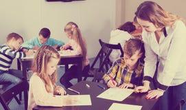Ragazzi e ragazze con il disegno dell'insegnante Immagine Stock