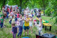Ragazzi e ragazze divertendosi, bolle di cattura Immagine Stock