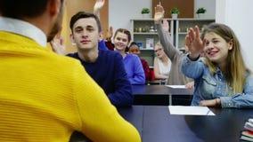 Ragazzi e ragazze nella classe pronta a dare risposta alla domanda dell'insegnante video d archivio