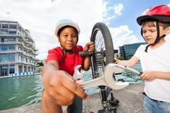 Ragazzi felici che riparano insieme bici all'aperto di estate immagine stock libera da diritti
