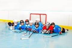 Ragazzi felici e ragazze che mettono sulla pista di pattinaggio del hockey su ghiaccio fotografia stock libera da diritti