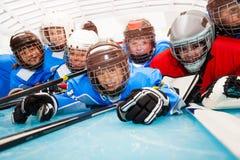 Ragazzi felici nella pista di pattinaggio sul ghiaccio mettente su uniforme dell'hockey immagine stock libera da diritti