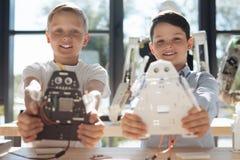 Ragazzi ottimistici che dimostrano le loro creazioni robot Immagine Stock Libera da Diritti