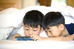 Ragazzi prescolari asiatici che giocano insieme sullo smartphone immagini stock libere da diritti