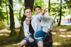 Ragazzi sorridenti divertendosi al campo da giuoco Bambini che giocano all'aperto di estate Adolescenti che guidano su un'oscilla Immagine Stock