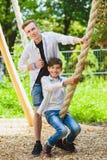 Ragazzi sorridenti divertendosi al campo da giuoco Bambini che giocano all'aperto di estate Adolescenti che guidano su un'oscilla Immagini Stock Libere da Diritti