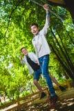 Ragazzi sorridenti divertendosi al campo da giuoco Bambini che giocano all'aperto di estate Adolescenti che guidano su un'oscilla Fotografie Stock
